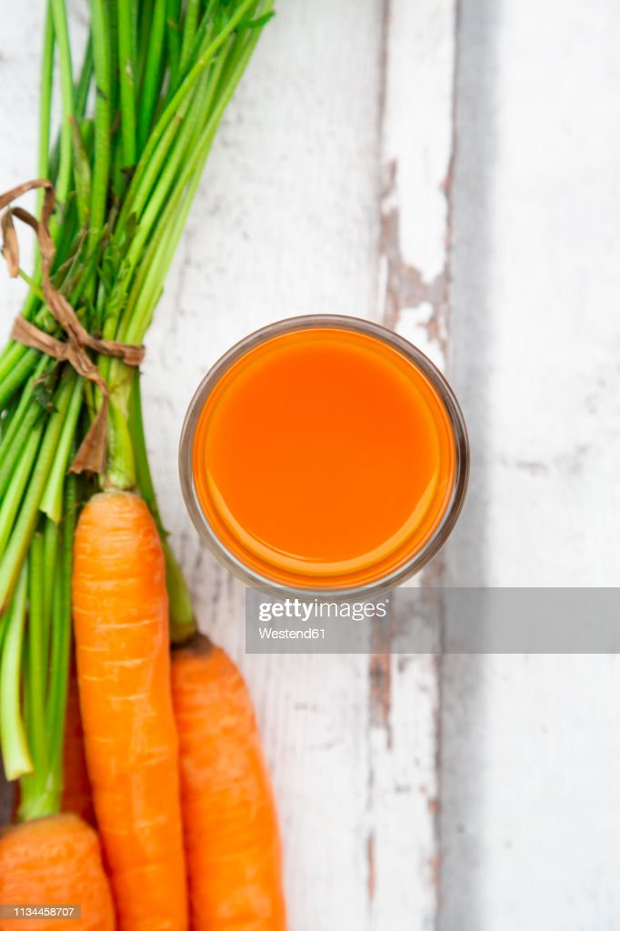 Carrots and glass of carrot juice on wood, from above : ストックフォト