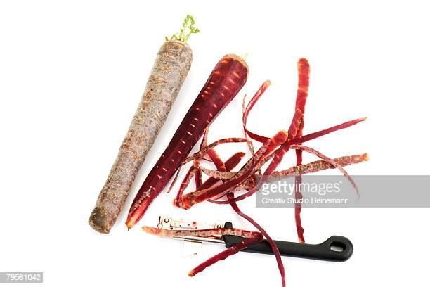 'Carrots (Purple Haze) and peeler, close-up'