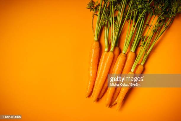 carrots over orange background - carrot stock pictures, royalty-free photos & images