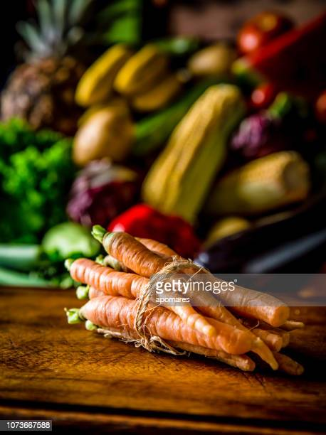Carrots with assorted organic tropical fruits and vegetables in a rustic kitchen background. Natural lighting