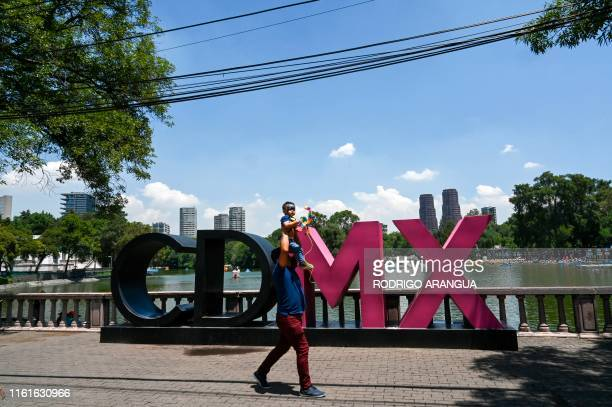 Carrying a child a man takes a walk on Chapultepec Park in Mexico City on August 14 2019 The World Urban Parks Organization awarded Chapultepec Park...