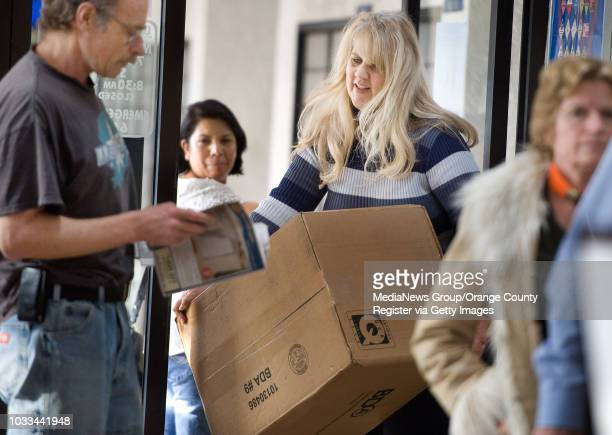 Carrying a Christmas gift to ship off to her son in Virginia Lisa Drew of San Clemente squeezes through the door of the Santa Ana Sunflower Ave post...