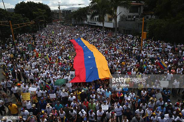 Carrying a giant Venezuelan flag thousands of antigovernment protesters march during a mass demonstraiton on March 2 2014 in Caracas Venezuela...