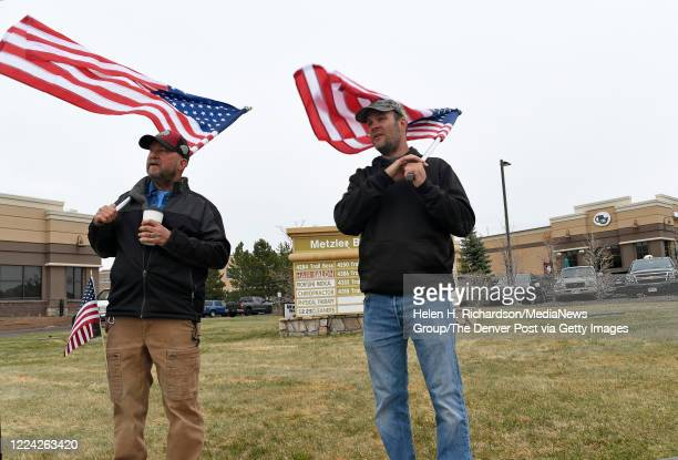 Carrying American flags Jed Gilman left and John Hulse right walk along Trail Boss Drive to show their support for CC Coffee Kitchen on May 11 2020...