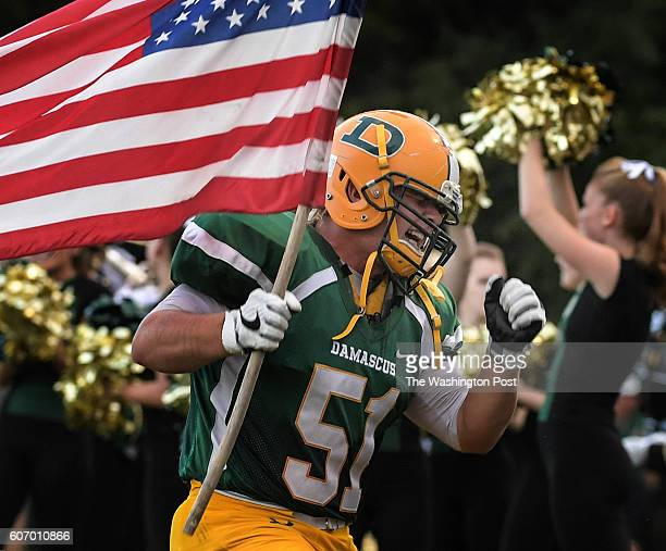 Carrying an American flag Damascus Hornets guard Mikey Bradshaw leads his team on to the field before the game between the Watkins Mills Wolverines...