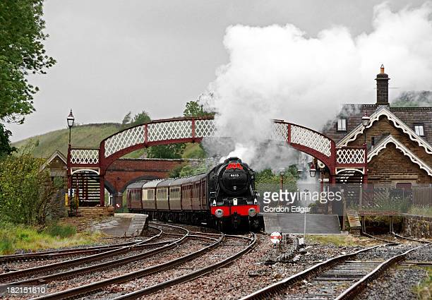 CONTENT] Carrying an 'Irish Mail' headboard Stanier 'Royal Scot' class 460 No46115 'Scots Guardsman' rounds the curve through Kirkby Stephen station...