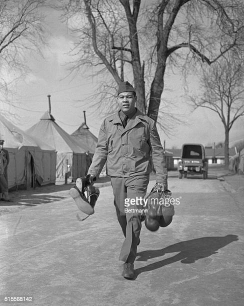 Carrying boxing gloves and shoes, Private Joe Louis heads for training quarters provided for him at fort Dix for his march 27, 1942 meeting with Abe...
