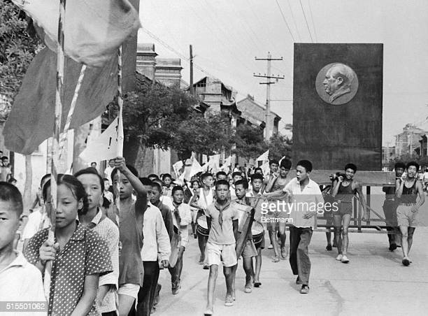 Carrying flags and beating drums Communist China's Red Guards march through a street in Peking The youths also display a huge portrait of their idol...