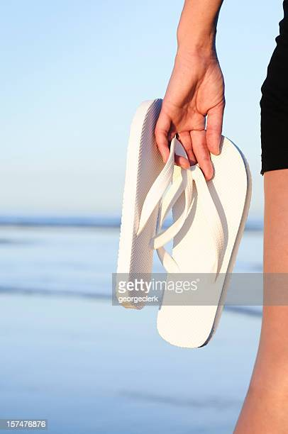 Carrying flip-flops on the beach