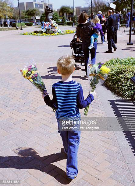 Carrying flowers Calvin Norvell son of Euless Police Officer David Norvell follows his mother Karen and little sister Ella to the growing memorial on...