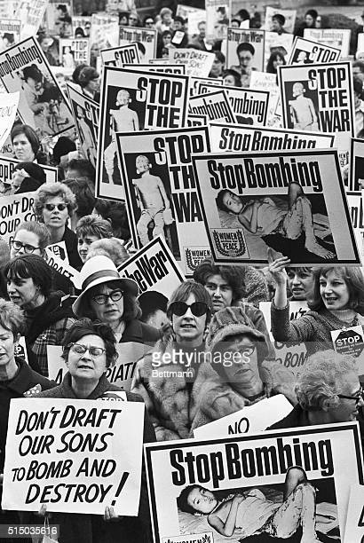 Carrying graphically illustrated antiVietnamese war posters members of the Women's Strike for Peace push their way to the doors of the Pentagon...