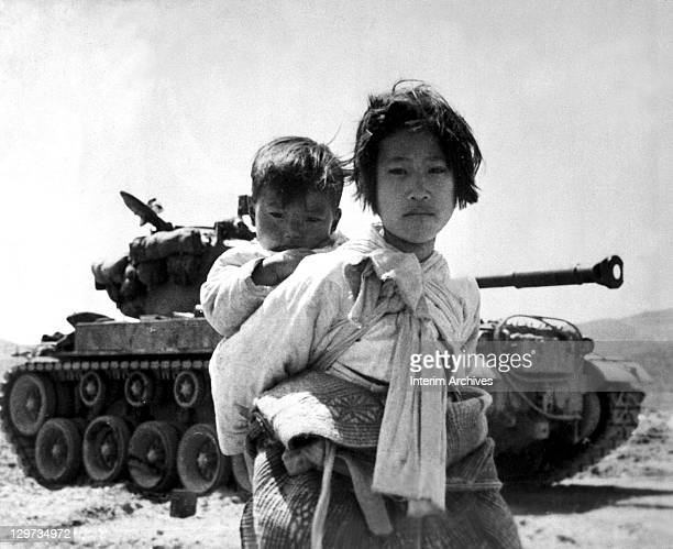 Carrying her baby brother on her back, a war weary Korean girl walks by a stalled M-26 tank, at Haengju, Korea, June, 1951.