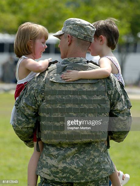 Carrying his daughters Molly and Emily Sgt Kenneth Messer walks to her car after a homecoming ceremony for 270 soldiers with the US Army's 2nd...