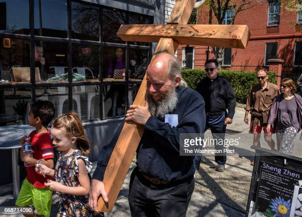 Carrying his homemade cross John Seeley along with youthful escorts passes by diners at a cafe as clergy and members of Memorial Episcopal Church...