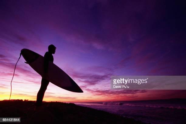 Carrying Surfboard on Beach at Dusk