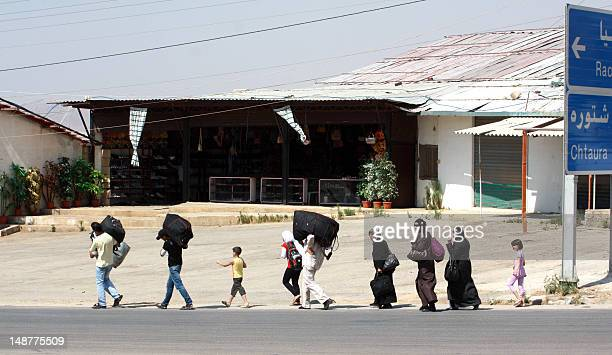Carrying their luggage people walk close to the area of the Masnaa crossing between the eastern Lebanon and neighboring Syria on July 19 as...
