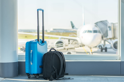 Carry-on in front of a plane 1067822456