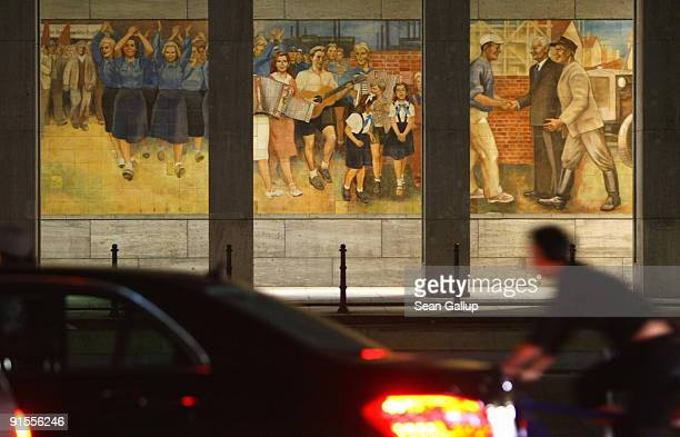 Cars and a bicyclist drive past a communistera mural depicting Socialist ideals on October 7 2009 in Berlin Germany The mural is located on the...