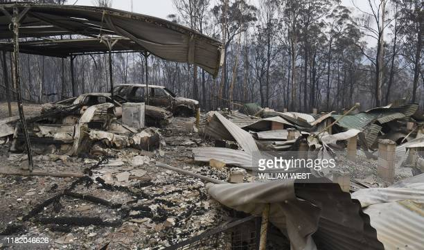 Cars and a house lay burnt out after bushfires impacted on houses and farmland near the small town of Glenreagh some 600kms north of Sydney on...