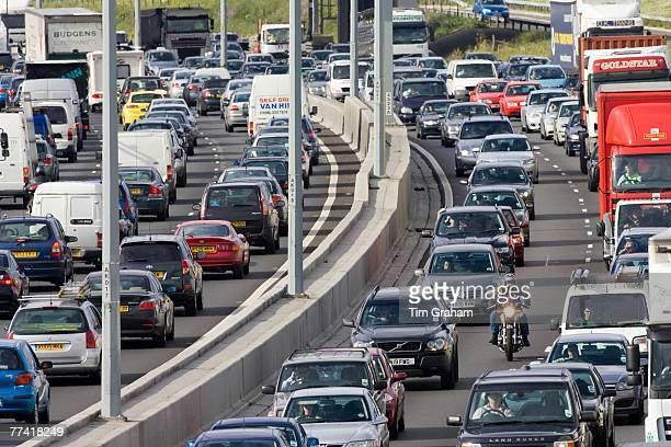 Cars and a motorcyclist in traffic congestion on M25 motorway near London United Kingdom