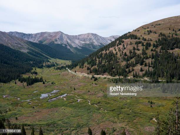 Cars and bicycle riders climb the hill leading over the 12095foot Independence Pass Colorado on September 15 2019 The pass is part of the Sawatch...