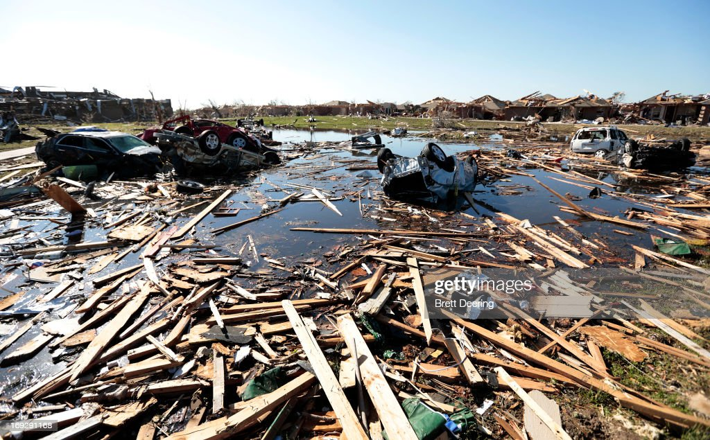 Cars and debris fill what had been a wetlands destroyed by the tornado at Briarwood Elementary School May 22, 2013 in Moore, Oklahoma. The two-mile-wide Category 5 tornado touched down May 20 killing at least 24 people and leaving behind extensive damage to homes and businesses. U.S. President Barack Obama promised federal aid to supplement state and local recovery efforts.
