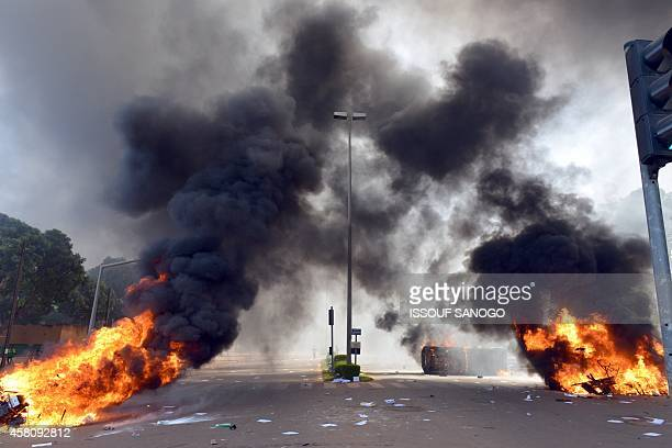 Cars and documents burn outside the parliament in Ouagadougou on October 30 2014 Hundreds of angry demonstrators in Burkina Faso stormed parliament...
