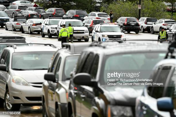 Cars and emergency vehicles are parked all along South Broadway as police direct parents and their kids across the busy intersection after picking...