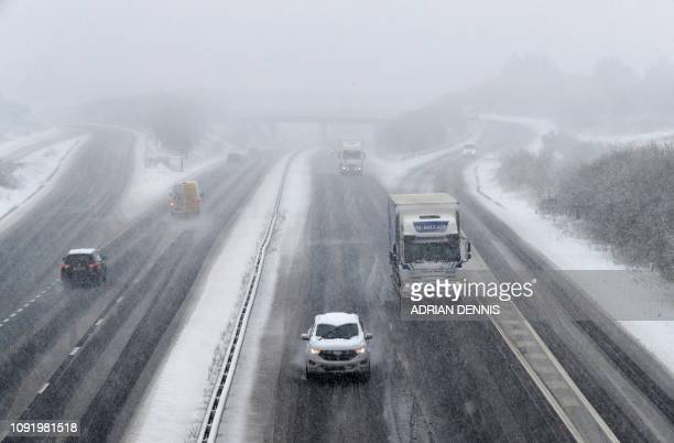 Cars and lorries are driven through snow and sleet as they travel along the A34 road near Chievely in Berkshire west of London on February 1 2019...