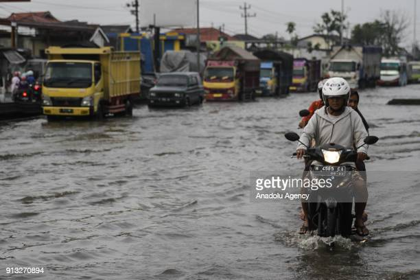 Cars and motorcycles wade through flood caused by the rising of sea level in SemarangDemak highway in Central Java Indonesia on February 2 2018 Local...