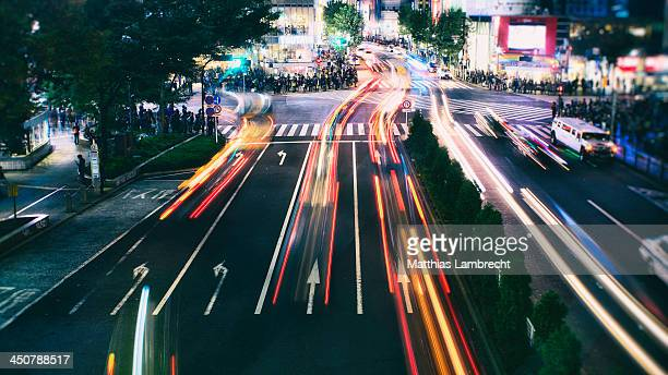 Cars and pedestrians in front of Shibuya at night