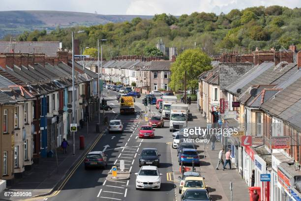 Cars and people pass shops along a road on April 25 2017 in Newport Wales The British Prime Minister Theresa May's visit to South Wales today to...
