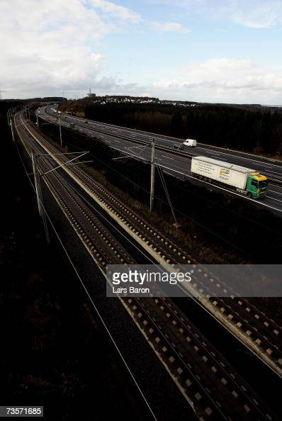 Cars and trucks are seen on a motorway beside railroad