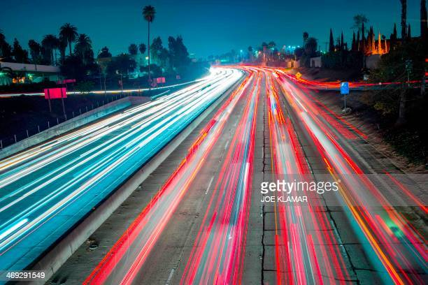 Cars and trucks are slowly moving during the evening's rush hour on Hollywood Freeway in Los Angeles California on February 13 2014 AFP PHOTO / JOE...