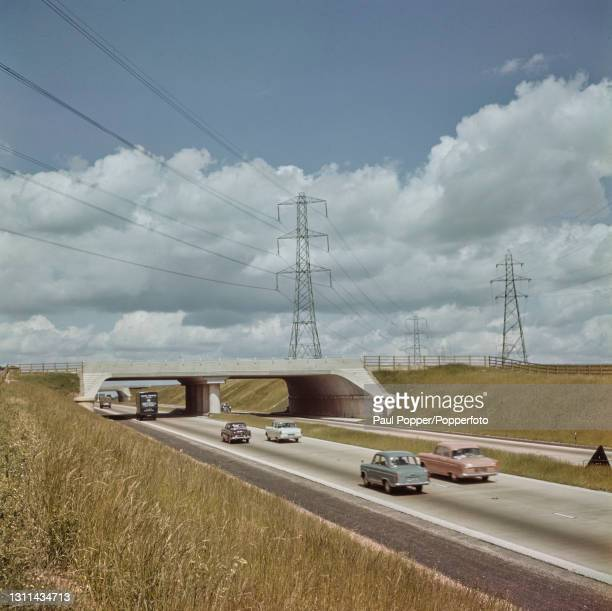 Cars and trucks drive along the M1 dual two-lane motorway, linking Watford in Hertfordshire and Rugby in Warwickshire through countryside in central...