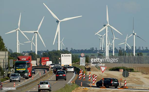 Cars and trucks on a highway drive past a windpark where wind turbines spin to produce electricity on August 19 2010 near Proesitz Germany Germany is...