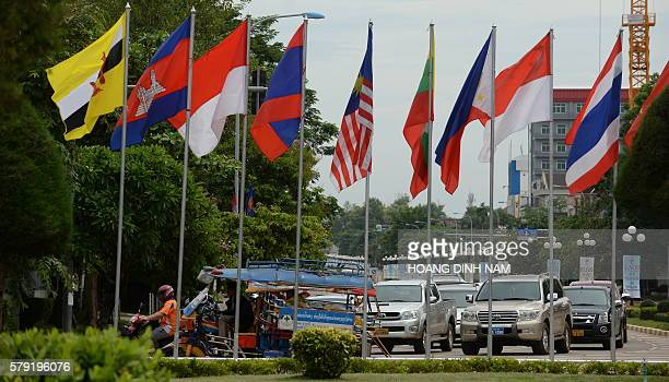 Cars and tuktuk ride past a row of ASEAN member countries' flags in the Laos capital of Vientiane on July 23 as the country hosts the 49th annual...