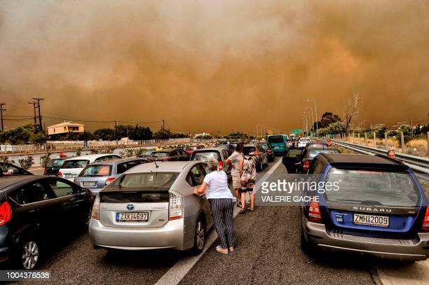 TOPSHOT Cars are blocked at the closed National Road during a wildfire in Kineta near Athens on July 23 2018 More than 300 firefighters five aircraft...