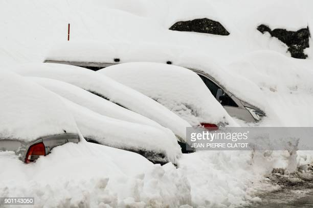 Cars are covered in snow in the ski resort of Les Menuires French Alps on January 4 2018 The French Alps were on maximum avalanche alert on January 4...