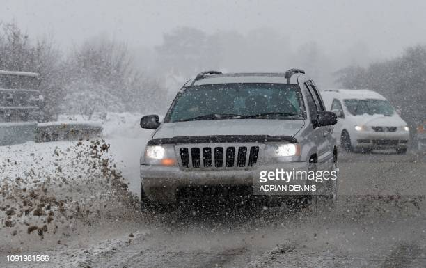 Cars are driven along a snow and slush covered road near Chievely in Berkshire west of London on February 1 2019 Snowfall and icy conditions were...