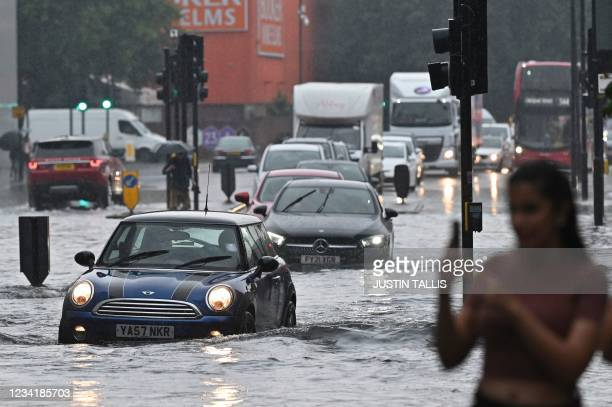 Cars are driven through deep water on a flooded road in The Nine Elms district of London on July 25, 2021 during heavy rain. - Buses and cars were...