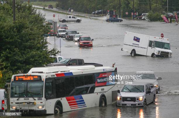 Cars are flooded as people walk though the flooded street of Little York on September 19 2019 in Houston Texas Gov Greg Abbott has declared much of...