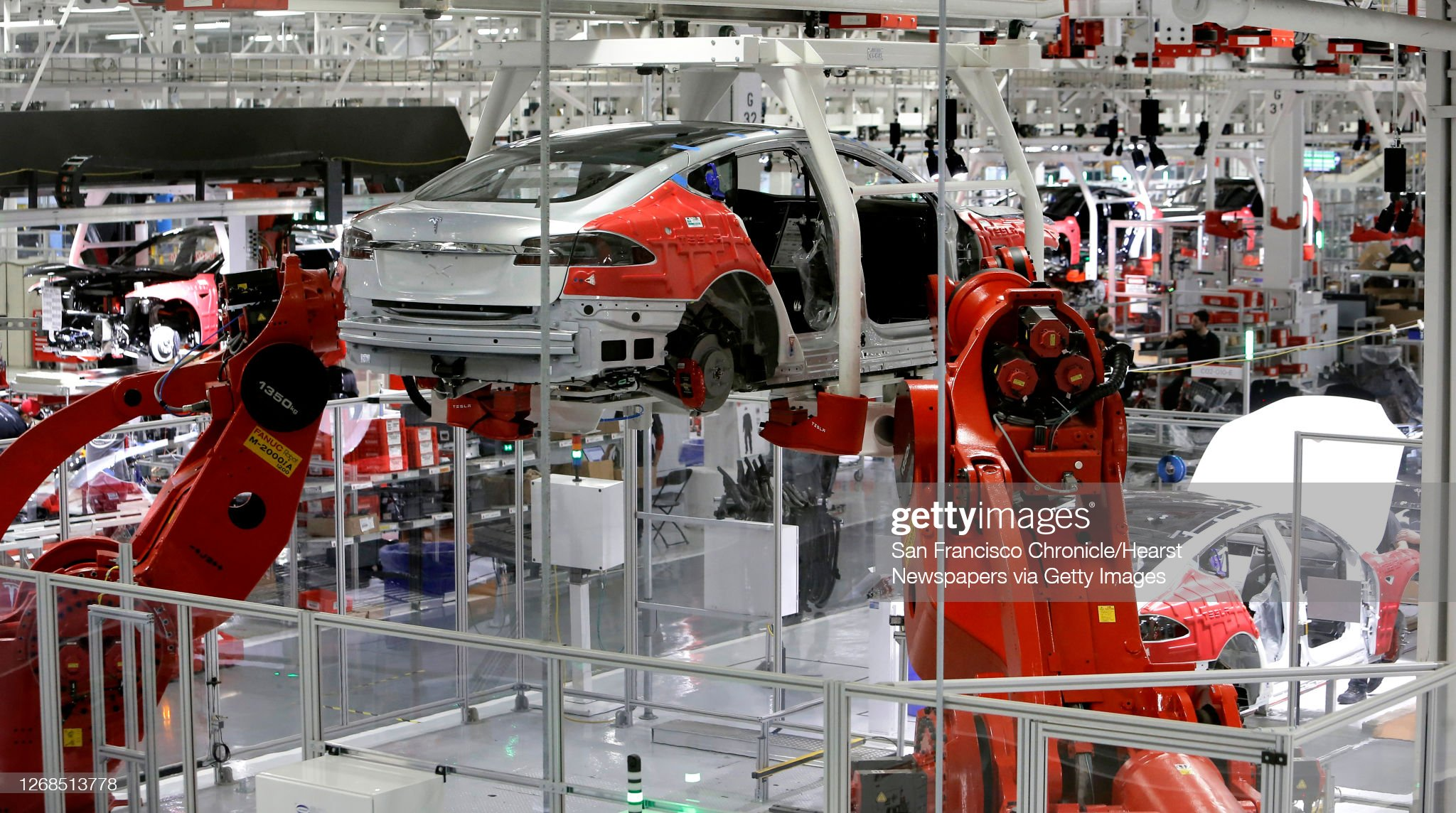 Tesla cars are moved through the assembly line by giant robot arms at Tesla Motors, California's only full-scale auto manufacturing plant, as seen on Thurs. Feb. 19, 2015, in Fremont, Calif. : News Photo