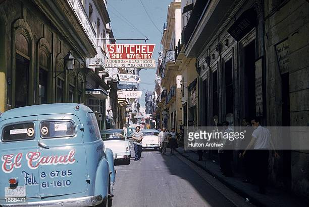 Cars are parked along a narrow street as pedestrians walk in the shade in Havana Cuba 1950s