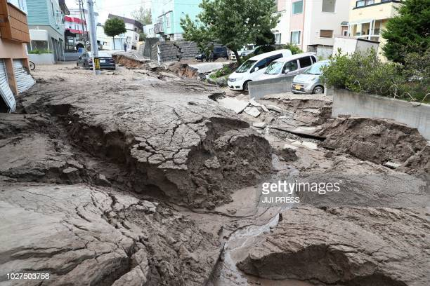 TOPSHOT Cars are parked along a road damaged by an earthquake in Sapporo Hokkaido prefecture on September 6 2018 A powerful 66magnitude quake rocked...
