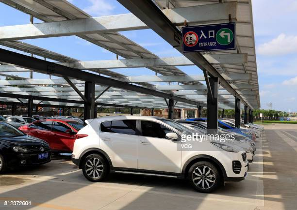 Cars are parked under solar panels at a photovoltaic parking lot on July 10 2017 in Chuzhou Anhui Province of China A photovoltaic parking lot with...