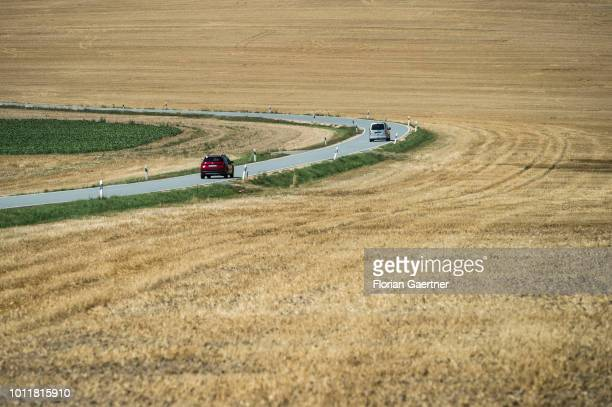 Cars are pictured on a road between dry fields on August 01 2018 in Koenigshain Germany Farmers complain harvest losses because of the dry weather...