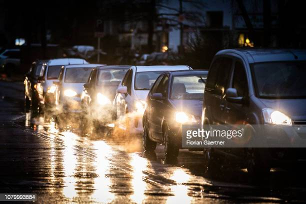 Cars are pictured on a wet street during blue hour on January 09 2019 in Berlin Germany