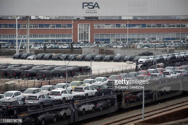 Cars are pictured parked in a lot in front of the French automaker PSA PeugeotCitroen Poissy plant on March 28 in Poissy outside Paris