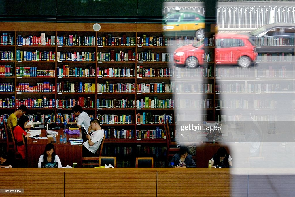Cars are reflected in a window as people read books at national library in Beijing on May 30, 2013. China's ruling Communist Party has called for greater political instruction for young university teachers, the education ministry has said.